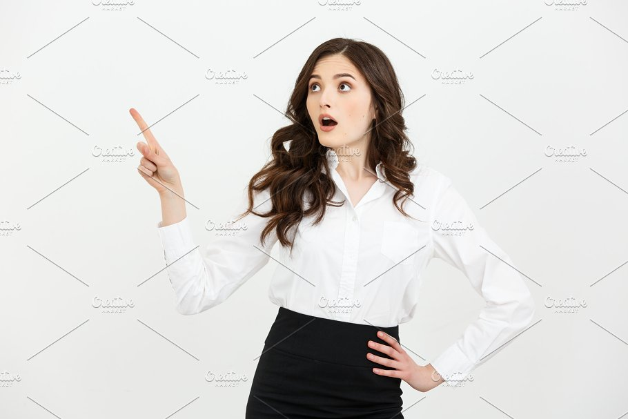 2a982a367e Business Concept  Portrait of surprised young businesswoman pointing finger  away to copy space. Isolated