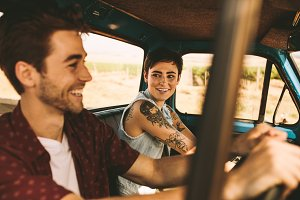 Young couple on a road trip driving