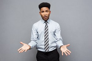 Business Concept - Confident cheerful young African American showing hands in front of him with disappointed expression over grey background.