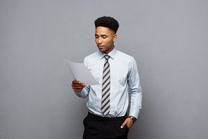 Business Concept - handsome young professional african american businessman concentrated reading on document paper.