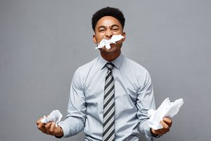Business Concept - Young angry African American businessman while eating balled report paper. Unsuccessful Project.