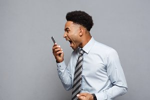 Business Concept - Stressful african american businessman shouting and screaming on mobile phone.
