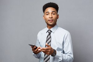 Business Concept - Happy handsome professional african american businessman texting on mobile phone.