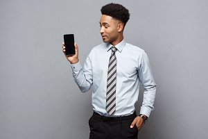 Business Concept - Happy handsome professional african american businessman showing mobile phone to client.