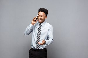 Business Concept - Cheerful professional african american businessman happy talking on mobile phone with client.