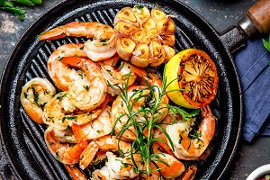 Grilled shrimps prawns on vintage grill pan, top view. Dark background