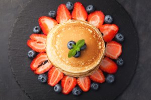 Delicious pancakes close up, with fresh blueberries, strawberries on a black stone background. Top view