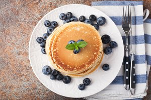 Delicious pancakes close up, with fresh blueberries on rusty background. Top view with copy space