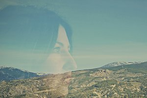 Double exposure of woman and mountainscape