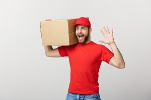 Delivery man doing surprise gesture holding cardboard boxes.
