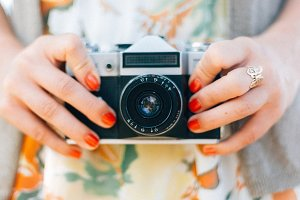 Female hands holding vintage camera