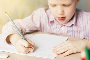 Cute little boy writing in notebook at the table.