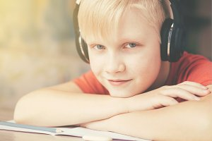Boy in headphones resting and listening to music .
