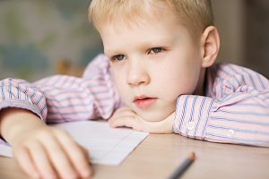 Cute  boy doing his homework and looking tired.