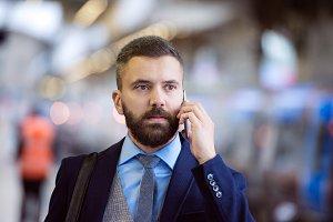 Businessman with smartphone, making a phone call, train platform