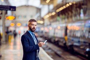 Hipster businessman with smartphone, waiting, train platform