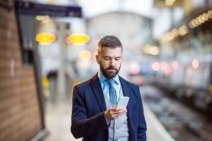 Hipster businessman with smartphone, waiting at the train platform