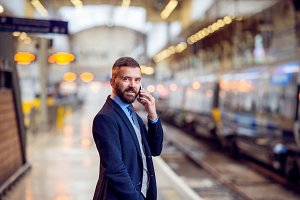 Hipster businessman with smartphone, making a phone call, platfo