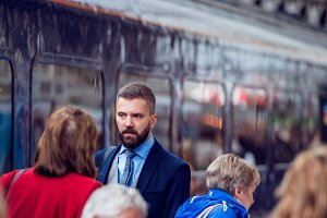 Hipster businessman walking, crowded underground platform, train