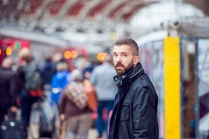 Hipster man waiting at the crowded train station