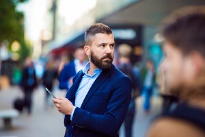 Hipster manager holding a smartphone outside in crowded street
