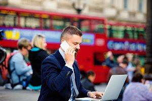 Manager with laptop and phone against  Londons red double-decker
