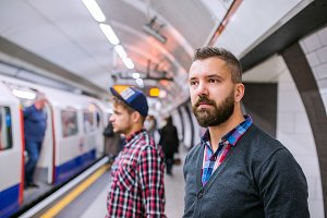 Two hipster men standing at the underground platform waiting