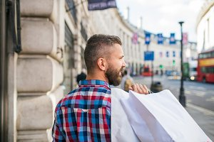 Hipster man shopping , streets of London, back view