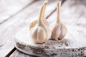 Fresh garlic on light wooden background