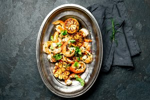Grilled roasted shrimps prawns on oval metal vintage plate, top vie. Slate background