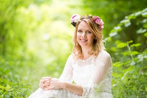 Bride in wedding dress with flower wreath, green nature.