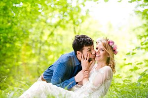Beautiful wedding couple outside in green forest.
