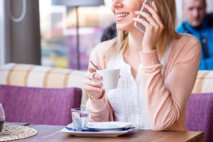 Woman in cafe drinking coffee, making a phone call