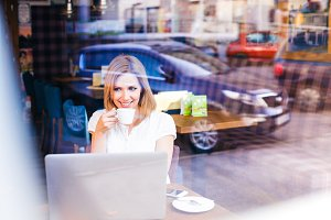 Double exposure, woman with notebook in cafe drinking coffee