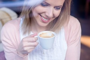 Unrecognizable woman with smartphone in cafe drinking coffee