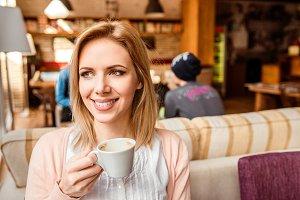 Woman in cafe drinking coffee, enjoying her espresso