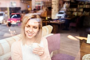 Woman in cafe drinking coffee, street reflection in window