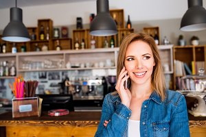 Blond woman standing at the bar, talking on phone
