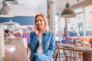 Blond woman sitting at the bar, talking on phone
