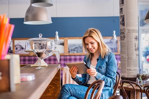 Blond woman sitting at the bar, writing on phone