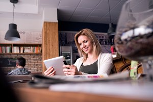 Blond woman with tablet in cafe drinking coffee