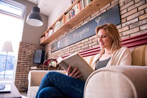 Blond woman with newspaper in cafe drinking coffee