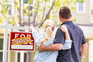 Couple Facing Sold Sign & House