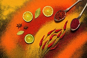 Background of various spices, red, orange, yellow. Paprika, turmeric, anise, bay leaf, chilli pepper, lime, saffron. Assorted spices.