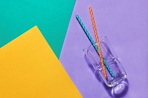 Empty glass with straws on a pastel colorful background, minimalist concept, flat lay.Concept of summer and drinks