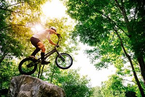 Cyclist making tricks in a rock