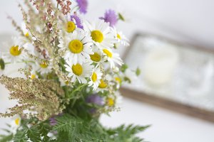Beautifull daisies and other flowers on a white table.