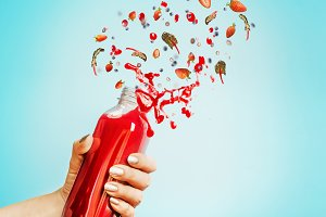 Female hand with red splash bottle