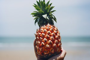 Man holding a pineapple at the beach