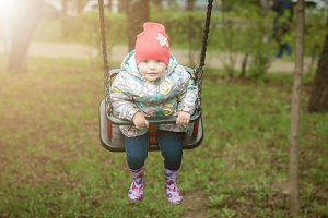 A small child is happily swinging on a swing